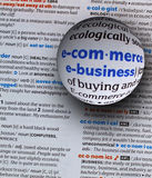 Focus on word ecommerce and ebusiness. Focus on word e-commerce and e-business on dictionary page by a glass globe magnifying and highlighting Royalty Free Stock Image