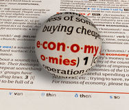 Focus on word economy. On dictionary page by a glass globe magnifying and highlighting Royalty Free Stock Image