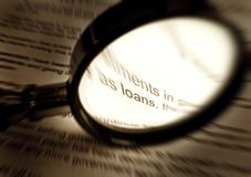 Focus on word loans in document. An image of a magnifying glass held over the fine print of a financial paper.  Processed to sepia brown monochrome and with Stock Photos