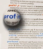 Focus on word profit. On dictionary page by a glass globe magnifying and highlighting Stock Photo