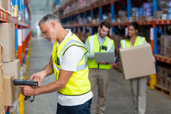 Focus of worker is working on cardboard boxes with his colleagues. In a warehouse Royalty Free Stock Photos