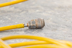 Focus yellow hose and coupler set on concrete Stock Photography