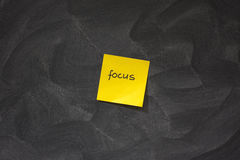 Focus on yellow sticky note against blackboard stock photo