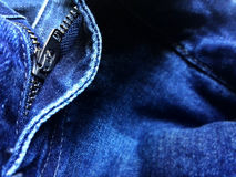 In focus zipper on blue jean fabric with slight defocus on right Stock Photo