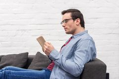 focused adult man reading book on couch stock photo