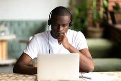 Focused African American man wear headphones, using laptop stock photos
