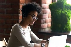 Focused African American woman wearing headphones using laptop. Ed African American woman wearing headphones using laptop, making writing notes, serious female royalty free stock photo