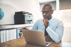Focused African entrepreneur deep in thought in a home office. Focused African businessman in a shirt and tie working online with a laptop at a desk in his home stock photos