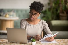 Free Focused African Student Looking At Laptop Holding Book Doing Research Royalty Free Stock Images - 144185369