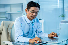 Focused asian businessman using calculator and laptop Royalty Free Stock Photography