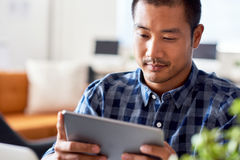 Focused Asian designer using a tablet in a modern office Royalty Free Stock Images