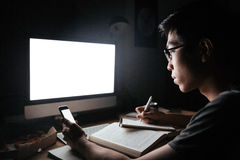 Focused asian man using blank screen mobile phone and computer Royalty Free Stock Photo
