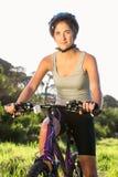 Focused athletic brunette sitting on mountain bike Royalty Free Stock Image