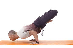 Focused athletic man posing in difficult yoga pose Royalty Free Stock Images
