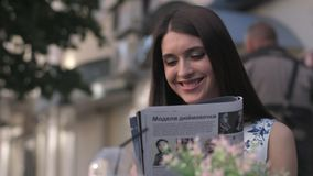 Focused attractive woman reading newspaper in cafe stock footage