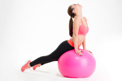 Focused attractive young fitness woman doing stretching on pink fitball Stock Photos