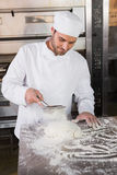 Focused baker sieving flour on the dough Stock Photos