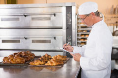 Focused baker writing on clipboard. In the kitchen of the bakery Royalty Free Stock Photography