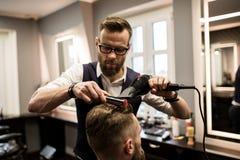 Focused barber drying customer hair. Portrait of focused barber drying customer hair Royalty Free Stock Photo
