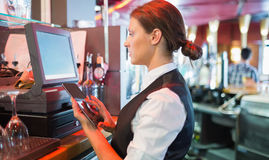 Focused barmaid using touchscreen till Royalty Free Stock Images