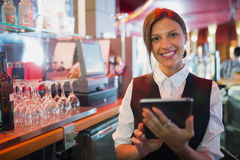 Focused barmaid using touchscreen till Royalty Free Stock Photos