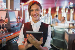 Focused barmaid using touchscreen till Royalty Free Stock Photography