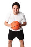 Focused basketball player in shorts and tshirt. Young attractive basketball player wearing a white tshirt with black shorts, holding a basketball. White Stock Photo