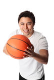 Focused basketball player in shorts and tshirt. Young attractive basketball player wearing a white tshirt with black shorts, holding a basketball. White Stock Images