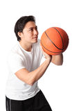 Focused basketball player in shorts and tshirt. Young attractive basketball player wearing a white tshirt with black shorts, holding a basketball. White Royalty Free Stock Photos