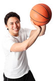 Focused basketball player in shorts and tshirt. Young attractive basketball player wearing a white tshirt with black shorts, holding a basketball. White Stock Photos