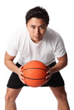 Focused basketball player in shorts and tshirt. Young attractive basketball player wearing a white tshirt with black shorts, holding a basketball. White Stock Image