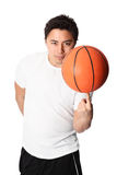 Focused basketball player in shorts and tshirt. Young attractive basketball player wearing a white tshirt with black shorts, holding a basketball. White Royalty Free Stock Image