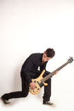 Focused bass player in black. Rock star Royalty Free Stock Images