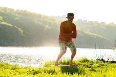 Focused bearded man is training on the balance board. On a green meadow next to river in the rays of summer sun. Back light, front view Stock Photo