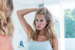 Focused beautiful young woman looking at herself in the bathroom mirror Stock Photo