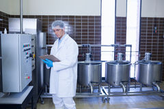 Focused biologist with safety gloves holding clipboard. In the factory Royalty Free Stock Photo
