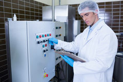 Focused biologist with safety gloves holding clipboard. In the factory Royalty Free Stock Images