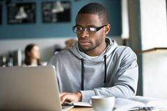 Focused black student studying online in coffeeshop. Serious black guy in glasses work at laptop sitting in coffeeshop, concentrated African American student royalty free stock images