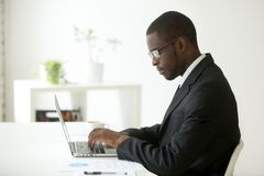 Focused black worker working at laptop at company workplace royalty free stock photos