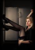 Focused. Blond woman sitting in doorway watching focused towards light royalty free stock photo