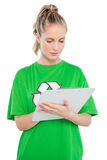 Focused blonde activist writing on clipboard Royalty Free Stock Photography
