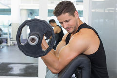 Focused bodybuilder lifting heavy black dumbbell Stock Photography