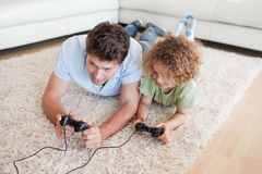Focused boy and his father playing video games Stock Images