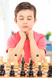 Focused boy playing chess seated at table indoors Stock Image