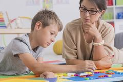 Focused boy and pretty psychotherapist. During therapy in colorful classroom Royalty Free Stock Images