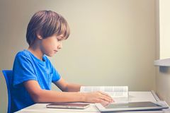 Focused boy reading a book. Tablet computer and mobile phone near to him at the table Stock Photo