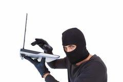 Focused burglar hacking into laptop Stock Photography