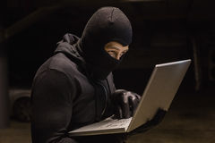Focused burglar standing holding laptop Royalty Free Stock Images