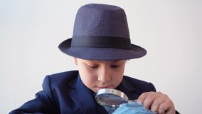 Focused business boss checking money banknotes with magnifying glass in office. Amazed little boy looking hundred dollar. Bills through magnifier in business stock footage