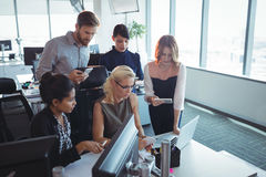 Focused business colleagues working together while using technologies. At office Stock Images